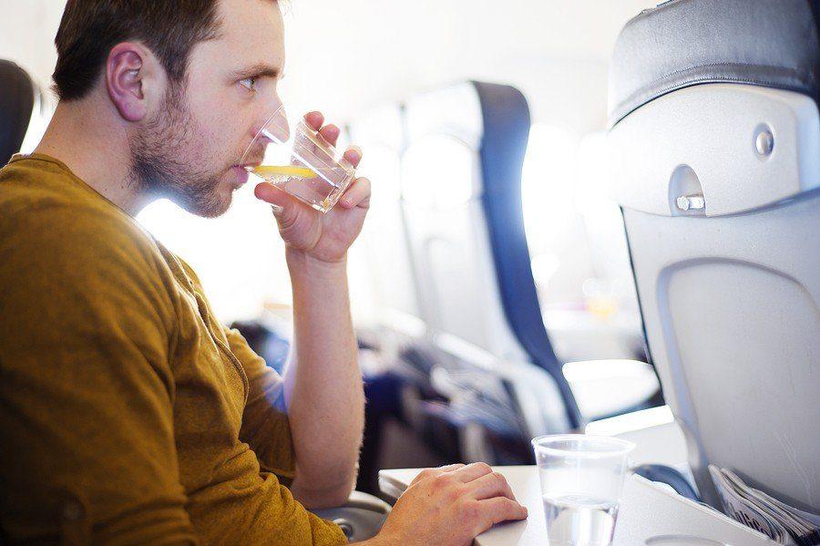 мужчина пьет в самолете
