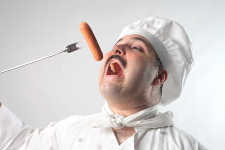 повар ест сосиску