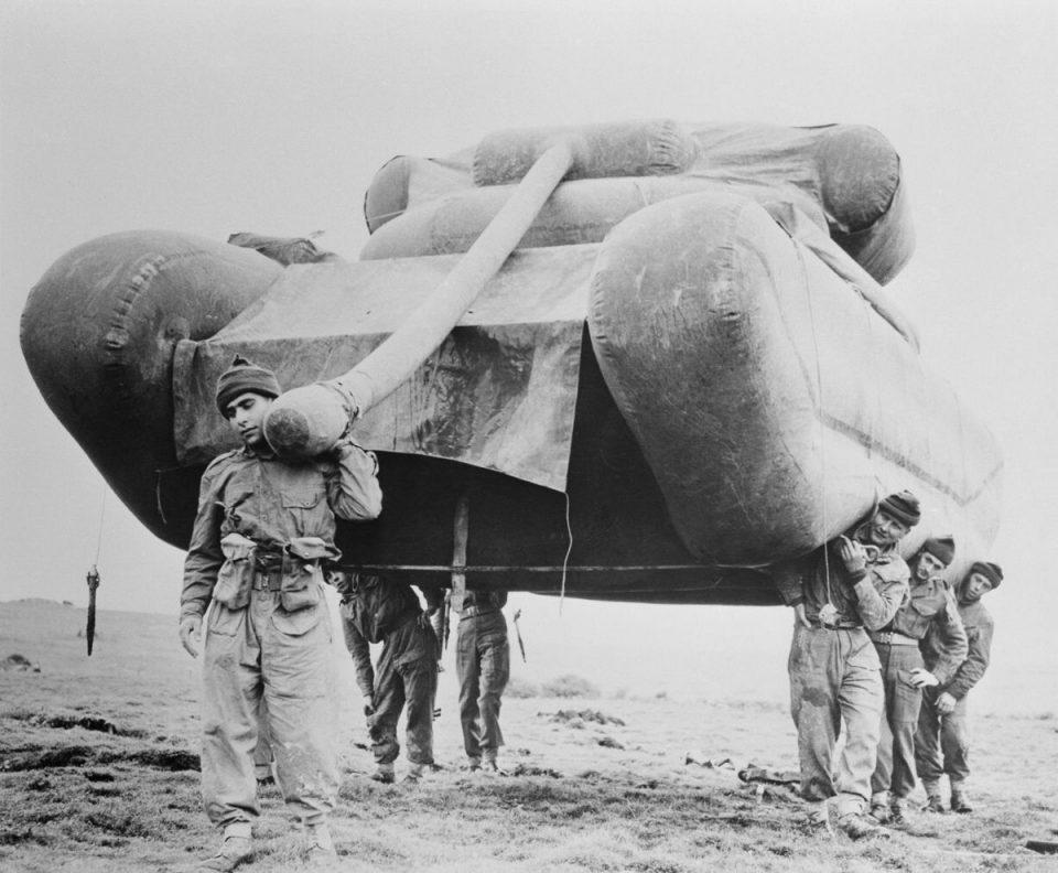 1954г. Британские солдаты поднимают надувной муляж танка во время учений на равнине Солсбери.