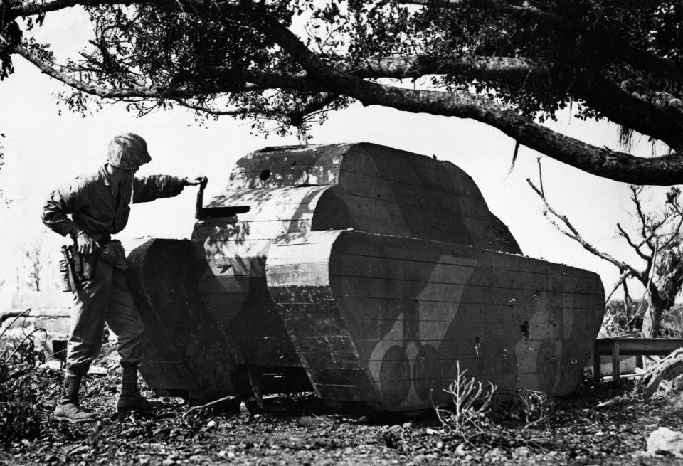 1945г. Морской пехотинец армии США осматривает деревянную планку в муляже японского танка на Окинаве.